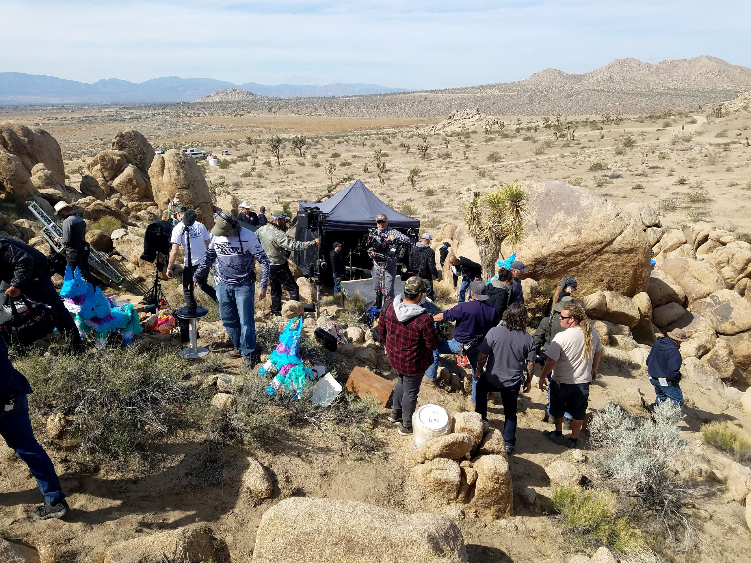 Filming a scene with the crew standing on rocks in the desert
