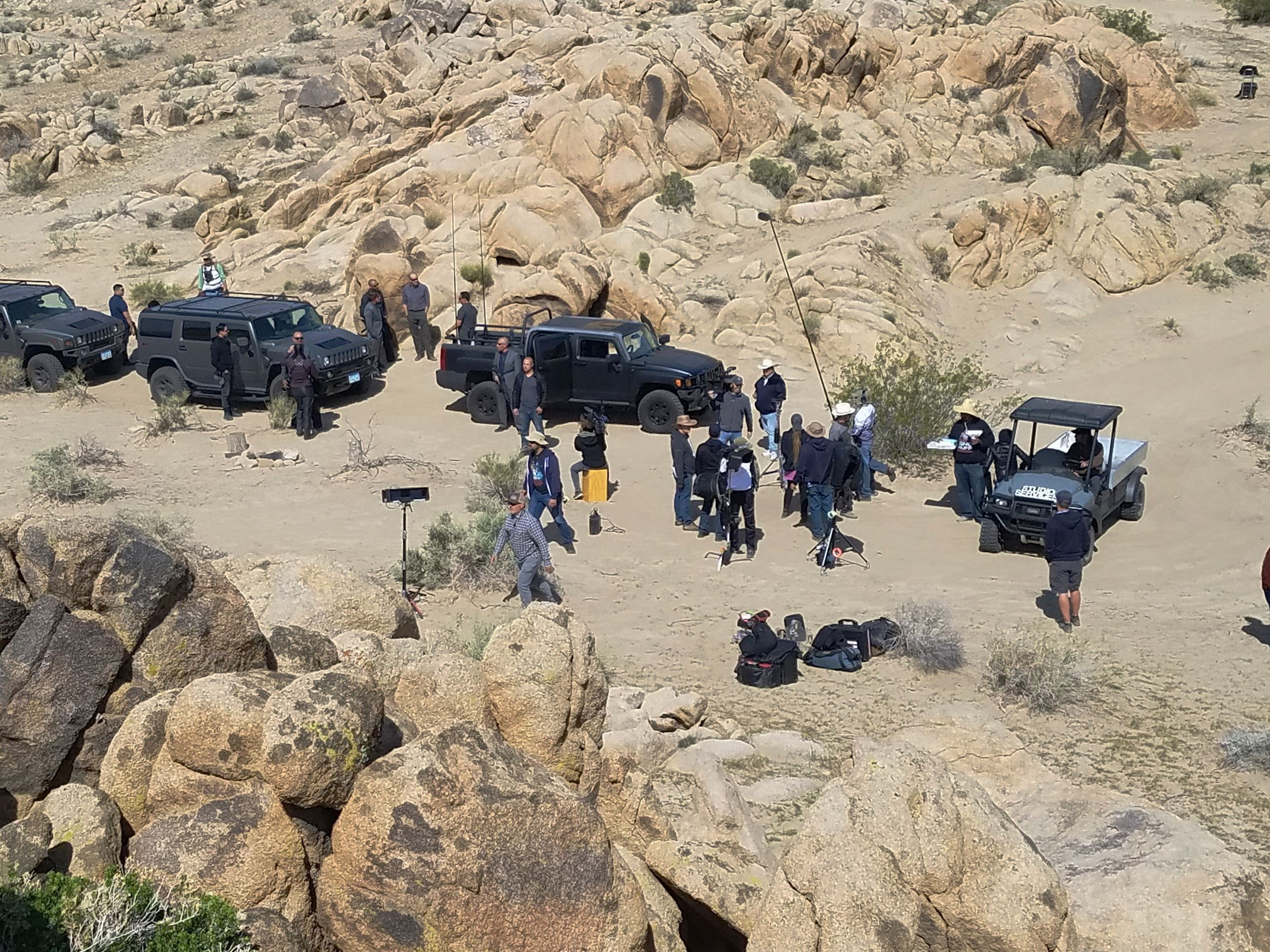Long shot of crew filming by the rocks in the desert