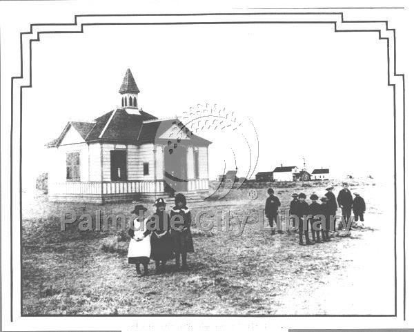 Children standing in front of a school house